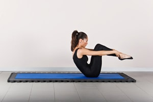 Woman holding sat on an exercise mat pulling her knees up to her chin and stretching her arms out infront of her. A common pilates position.