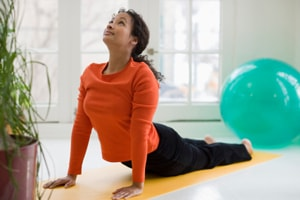 A woman laid on her front pushing her upper body off the ground using her arms. A common pilates position.