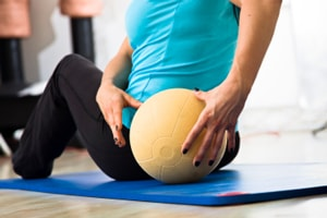 A member of a pilates class exercising with a medicine ball.
